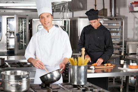cocinas industriales: Joven Chef Preparando Spaghetti Foto de archivo