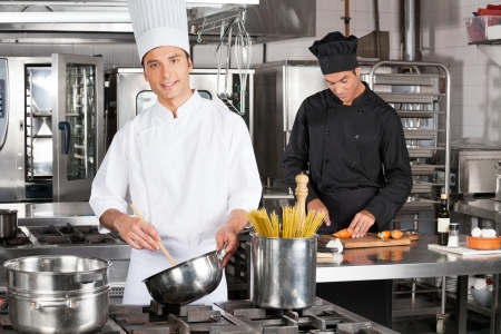 industrial kitchen: Young Chef Preparing Spaghetti Stock Photo