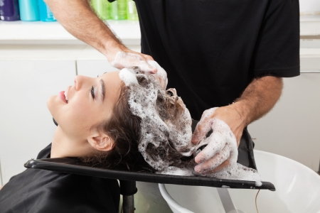 woman washing hair: Client Getting Hair Washed By Hairstylist