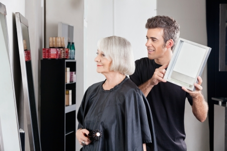 Hairstylist Showing Finished Haircut To Woman photo