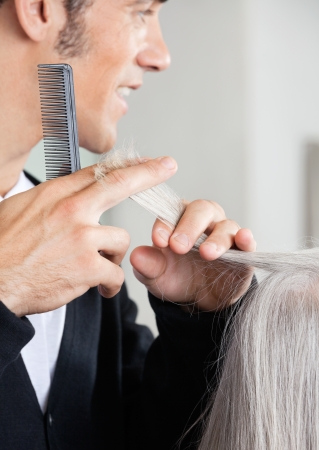 Hairdresser Cutting Senior Woman s Hair At Salon photo
