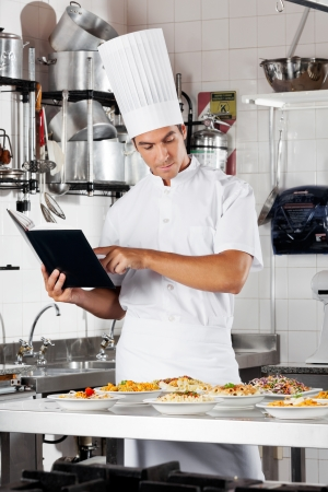 Chef Going Over Cooking Checklist Stock Photo - 18236572