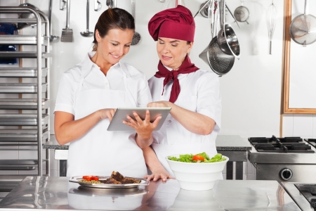 Happy Female Chefs Using Digital Tablet Stock Photo - 18236579