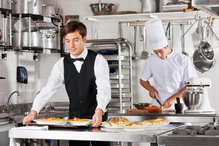 hotel staff: Waiter And Chef Working In Kitchen