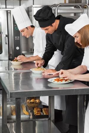 garnishing: Chefs Garnishing Pasta Dishes