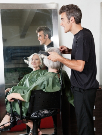 hair stylist: Hair Stylist Straightening Customer s Hair Stock Photo
