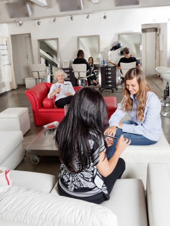 Woman Having Manicure With Customers Waiting At Parlor photo
