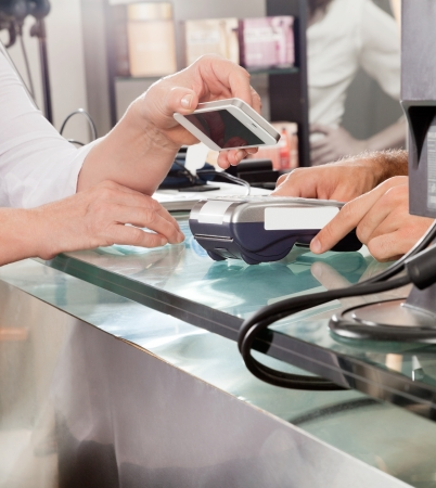 Customer Paying With Mobilephone Using NFC Stock Photo - 18236571