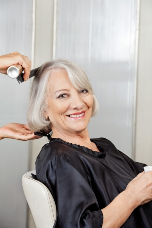Senior Woman Getting Hair Styled In Salon photo