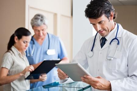 male doctor: Medico maschio che tiene digitale Tablet