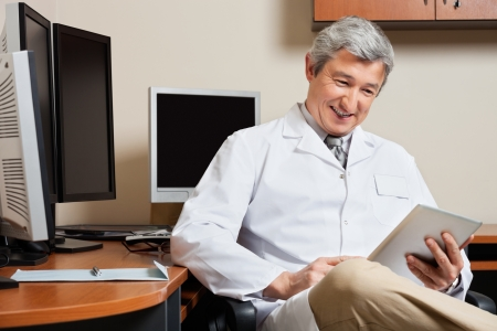 Happy Doctor Holding Digital Tablet photo