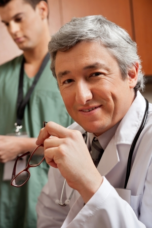 Mature Doctor Holding Glasses Stock Photo - 18261993
