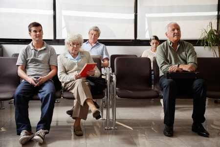 healthcare visitor: People Sitting In Hospital Lobby Stock Photo