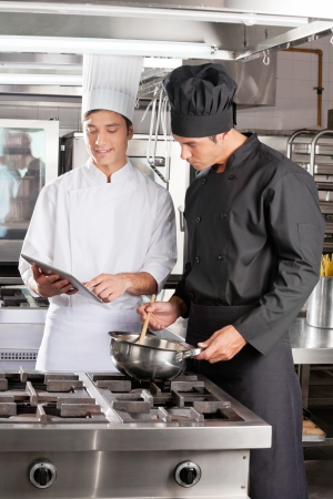 Young Chefs With Digital Tablet Preparing Food Stock Photo - 18262075