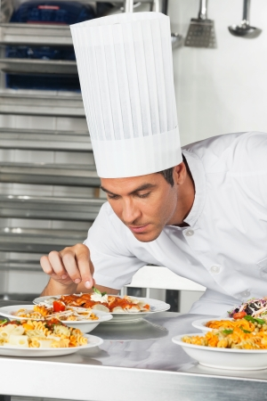 Male Chef Garnishing Pasta Dishes Stock Photo - 18261313