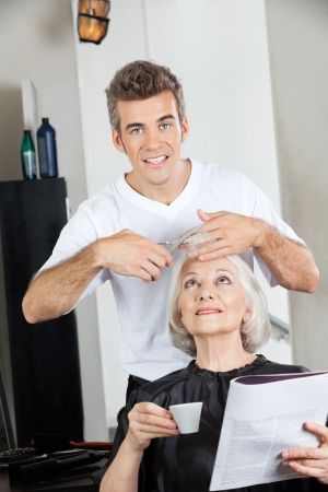 Hairstylist Cutting Woman s Hair In Salon Stock Photo - 18261847