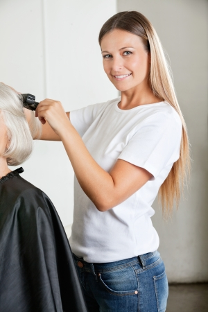 Hairdresser Ironing Female Client s Hair photo