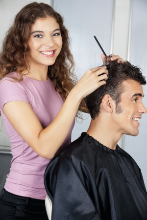 Happy Female Hairdresser Cutting Client s Hair photo