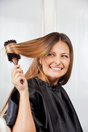 Woman Brushing Hair In Salon photo
