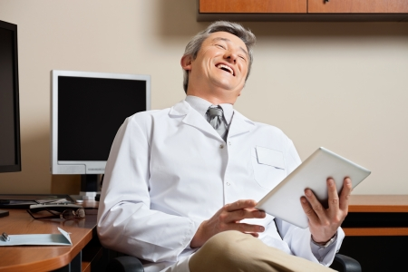 Cheerful Doctor Holding Digital Tablet photo