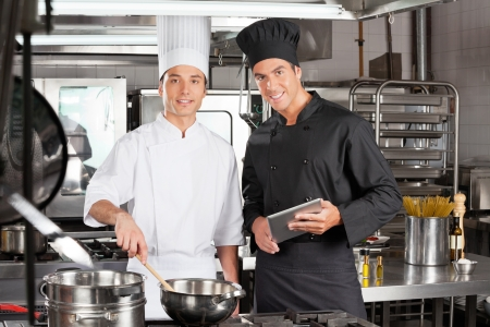 Happy Chefs With Digital Tablet Cooking Food photo