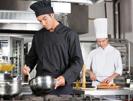 commercial kitchen: Chef Cooking Food With Colleague Chopping Vegetable Stock Photo