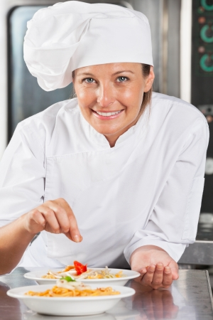 female chef: Happy Chef Adding Spices To Food