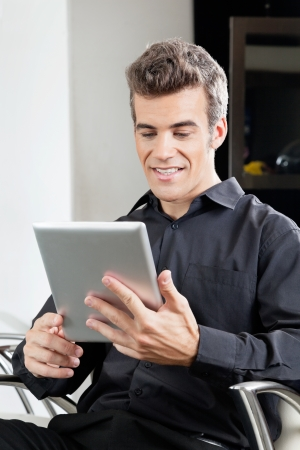 Male Client Using Digital Tablet In Salon photo