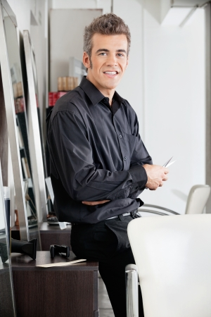 Male Hairstylist With Scissors Leaning On Cabinet Stock Photo - 18291745