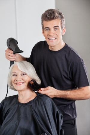 Hairstylist With Dryer Setting Up Woman s Hair photo