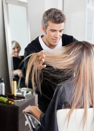 Hairdresser Attending Customer In Hair Salon photo