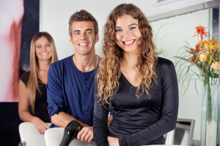 Happy Hairdressers Standing In Salon photo
