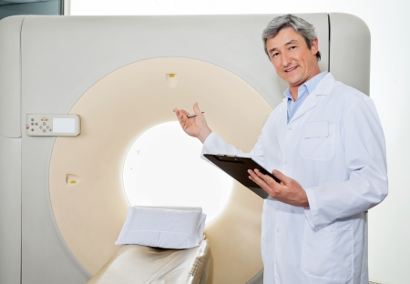 Male Doctor Presenting The CT Scan Machine photo