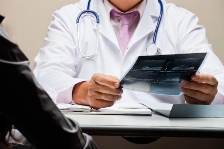 medico con paciente: Radi�logo En El Escritorio holding x-ray