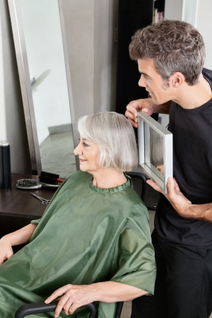 parlour: Hairdresser Holding Mirror Behind Senior Woman Stock Photo