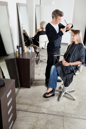 beauty parlor: Hairdresser Cutting Client s Hair In Parlor