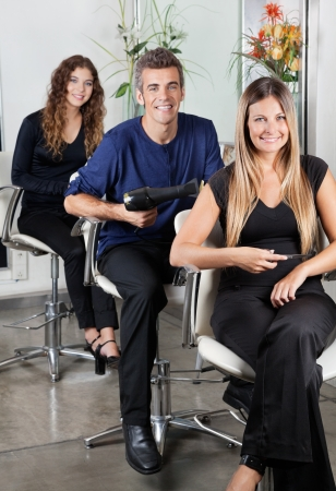 Confident Hairstylists sitting In Salon photo