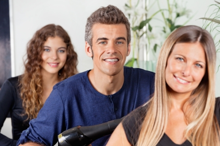 Male And Female Hairstylists At Salon photo