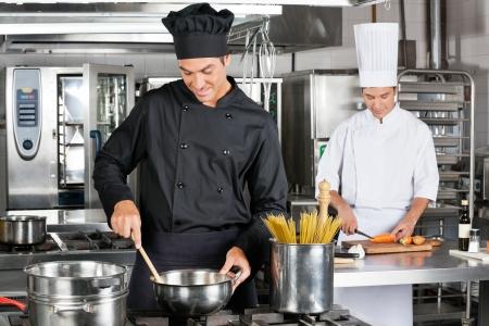 stirring: Professional Chefs Preparing Spaghetti
