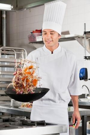 chef cocinando: Chef Verduras dando vueltas en Wok Foto de archivo