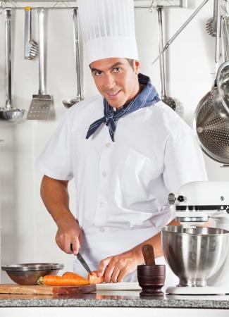 cocinas industriales: Masculino joven chef de corte Zanahorias Foto de archivo