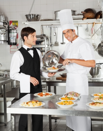 Chef Giving Pasta Dish To Waiter photo