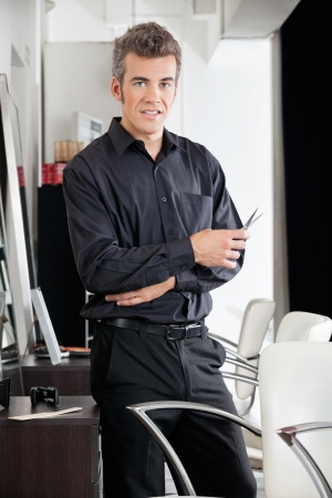 Male Hairstylist With Scissors At Salon photo