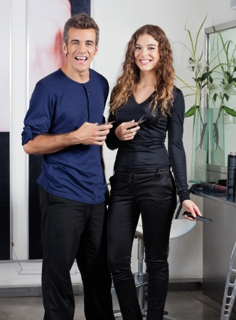 Hairdressers Holding Scissors While Standing In Salon photo