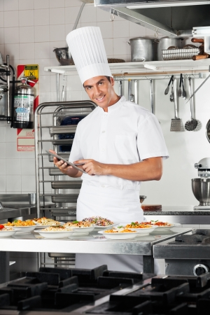 Happy Chef With Digital Tablet Checking List Of Pastas photo