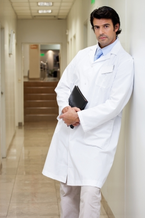 Serious Male Doctor Holding Book photo