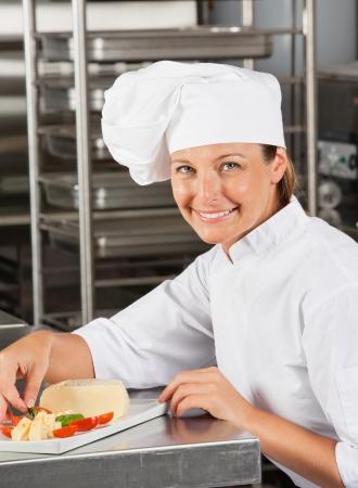 garnishing: Happy Female Chef Garnishing Dish