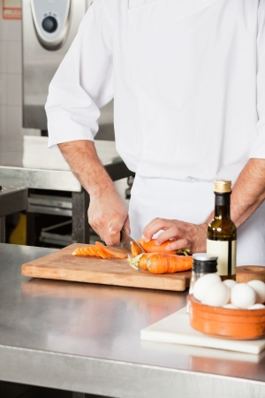 Chef Cutting Carrots At Kitchen Counter photo