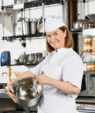 Chef Holding Wire Whisk And Mixing Bowl photo