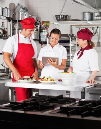Chefs Using Digital Tablet In Kitchen photo